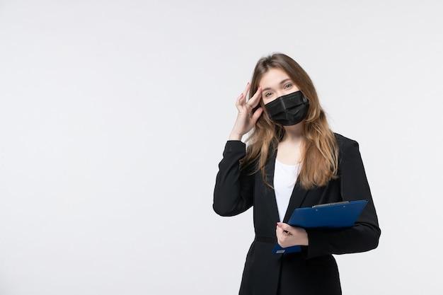 Imprenditrice in tuta che indossa la sua maschera medica e tiene documenti che soffrono di mal di testa su bianco