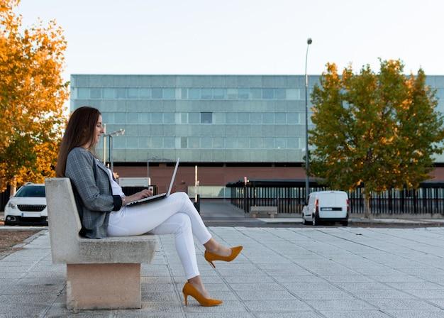 그녀의 노트북으로 공원 벤치에서 일하는 여성 기업가. 비즈니스 개념