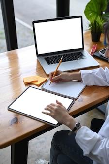 디지털 태블릿으로 작업하고 노트북에 메모하는 여성 기업가.