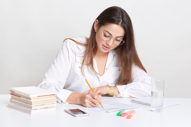 Female entrepreneur writes organisation plan, sits at desktop, uses books and pencil, drinks fresh water from glass, concentrared on work, wears round optical glasses, isolated on white
