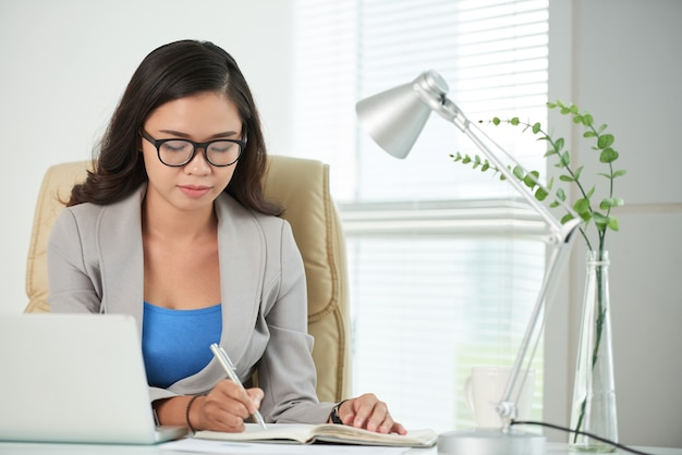 メモ帳で書く女性起業家