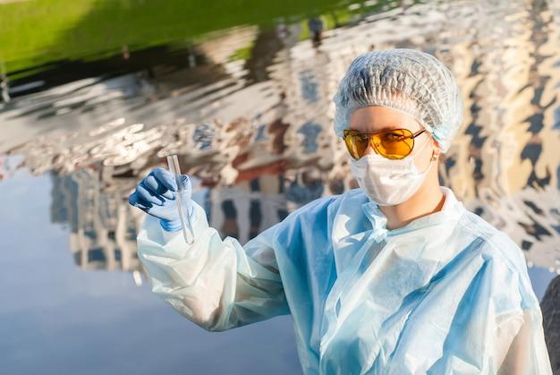 女性の疫学者が水で試験管を実演