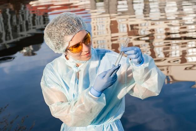女性の疫学者が水で試験管を見る