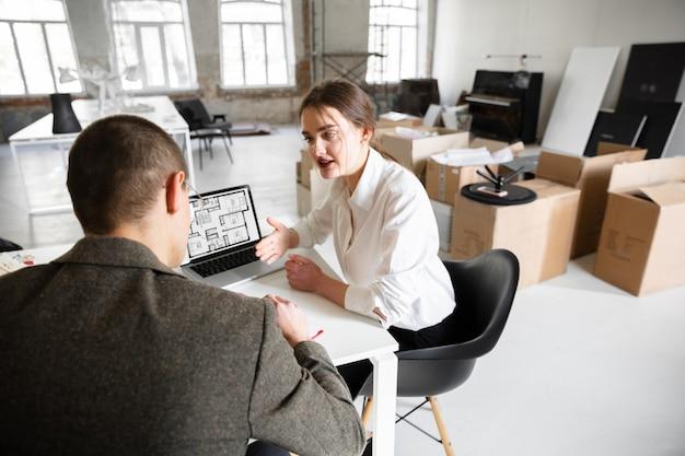 Женщина-агент по недвижимости показывает новый дом молодому человеку после обсуждения планов строительства нового дома Premium Фотографии