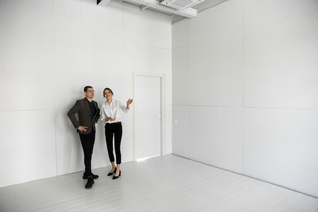 Женщина-агент по недвижимости показывает новый дом молодому человеку после обсуждения планов строительства нового дома