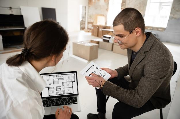 Женский агент по недвижимости показывает новый дом молодому человеку после обсуждения планов дома, переезда, новой концепции дома