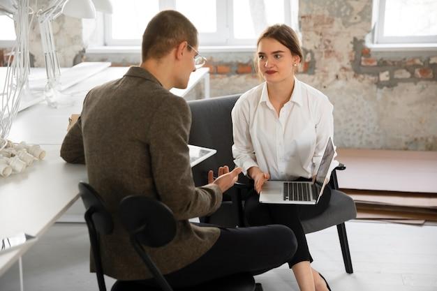 Agente immobiliare femminile che mostra una nuova casa a un giovane dopo una discussione sui piani della casa che spostano il nuovo concetto di casa