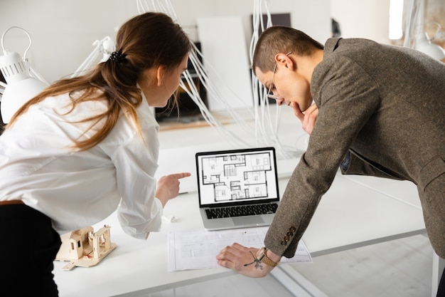 Female estate agent showing new home to a young man after a discussion on house plans moving new home concept