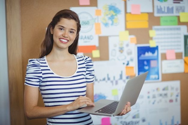 Женский исполнитель держит ноутбук в офисе
