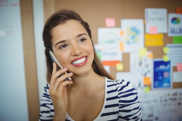 Исполнительный женщина разговаривает по мобильному телефону в офисе
