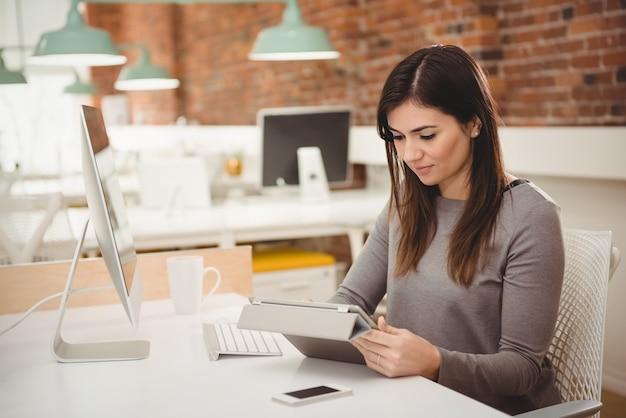 데스크에서 디지털 태블릿을 사용하는 여성 임원