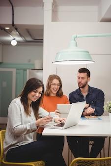 Женщина-руководитель с помощью мобильного телефона и ноутбука в офисе