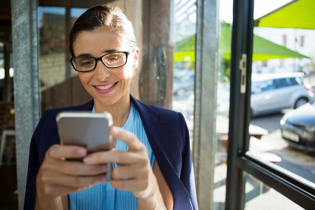 カフェで携帯電話を使用して女性の幹部