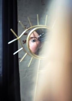 거울 속의 여성의 눈과 손은 눈썹, 미용 산업 및 미용 근처에 영구적인 메이크업 스틱을 들고 있습니다.