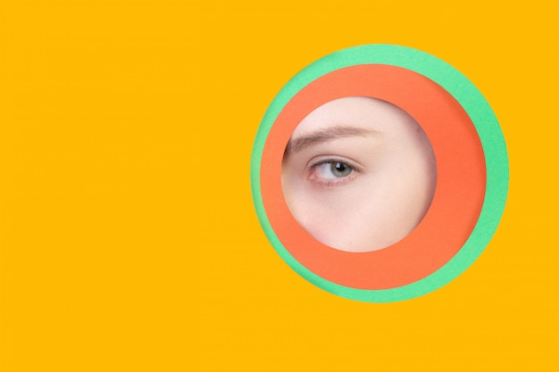 女性の目を見て、オレンジ色の背景の丸い円を覗く