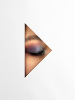 Female eye with make-up through the white triangle in white paper.