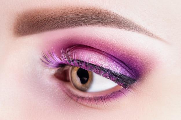 Female eye with pink violet shadows and false eyelashes