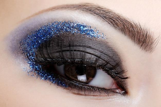 Женский глаз со стильным и модным блеском макияжа