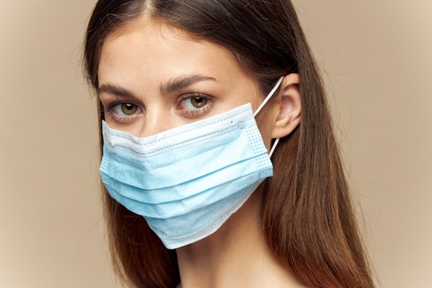 Женское лицо в медицинской маске, модель здравоохранения, бежевый портрет