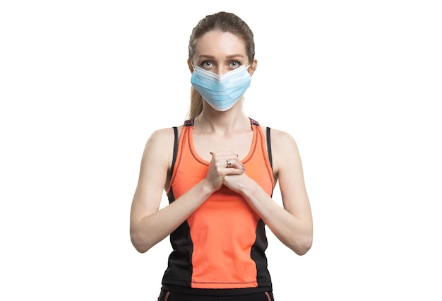Female in a face mask and orange sport suit working out during the quarantine
