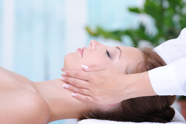 Female face massage in the beauty salon - profile close-up