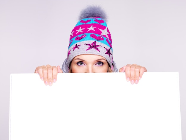 Женское лицо над белым плакатом. женщина в зимней шапке