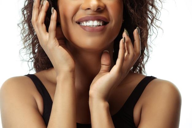 흰 벽에 고립 된 잘 관리 된 피부를 가진 여성 얼굴. 아프리카 계 미국인 아름다운 모델. 미용, 자기 관리, 체중 감량, 피트니스, 슬리밍 개념. 화장품 및 미용, 주입.