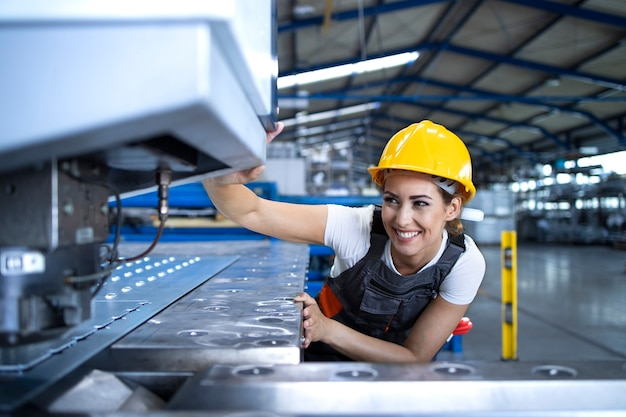 Работница фабрики в защитной форме и каске работает на промышленной машине на производственной линии