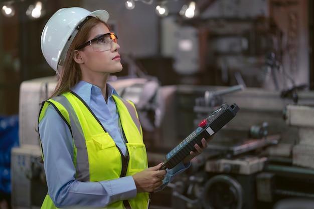 생산 공장을 만드는 기계에서 생산 라인을 검사하는 여성 공장 노동자