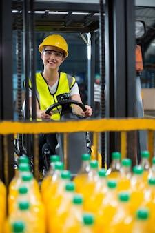 工場のフォークリフトにパックされたジュースのボトルを読み込む女性工場労働者