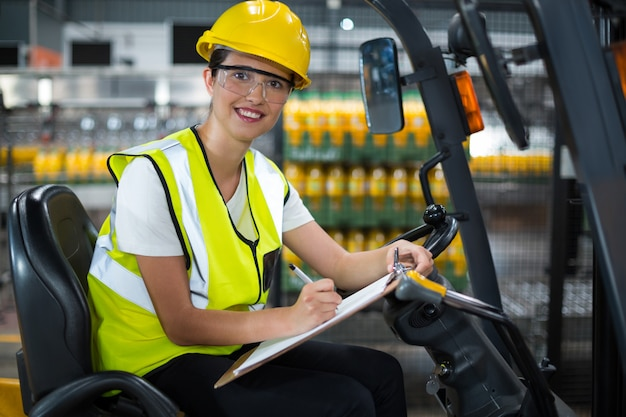 Female factory worker sitting on forklift and writing in clipboard at factory