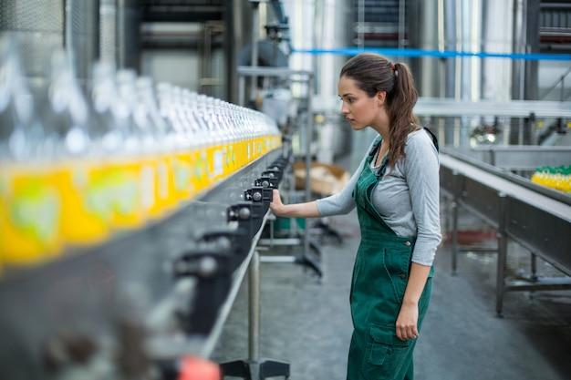 Работница фабрики стоит возле производственной линии