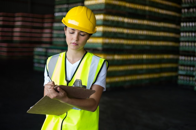 Female factory worker writing on clipboard in factory