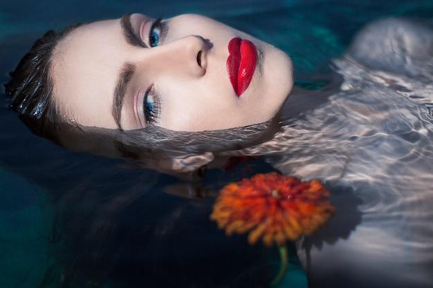 Женская светловолосая модель в авангардной косметике с красной помадой