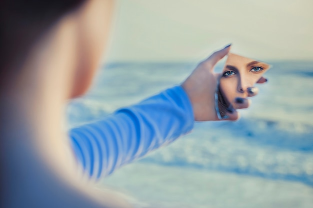 Female fair haired model in mirror looking herself