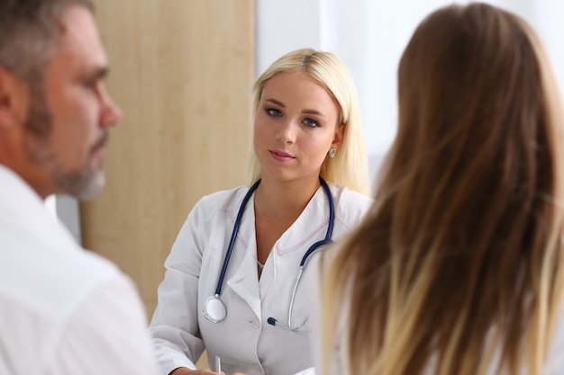 Female family doctor listen carefully young couple