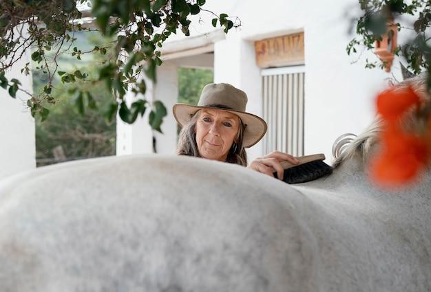 Coltivatore femminile che spazzola il suo cavallo al ranch
