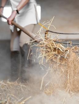 말이 마구간에서 건초를 청소하는 여성 농부
