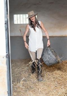 馬小屋から干し草を掃除する女性農家