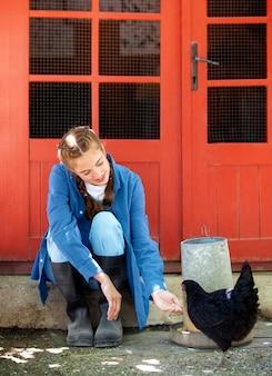 닭에게 먹이를 주는 여성 농부