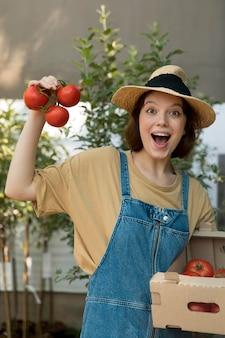 Contadina che tiene dei pomodori
