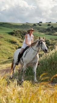 Agricoltore femminile passeggiate a cavallo nella natura all'aperto