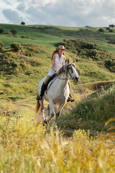 Female farmer horseback riding outdoors in nature