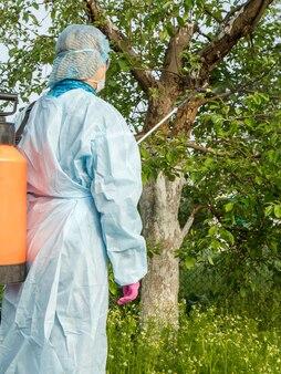 보호복을 입은 여성 농부가 봄 과수원에서 곰팡이 질병이나 해충의 사과 나무에 압력 분무기와 화학 물질을 뿌리고 있습니다.