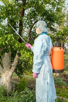 보호복을 입은 여성 농부가 여름 과수원에서 곰팡이 질병이나 해충의 사과 나무에 압력 분무기와 화학 물질을 뿌리고 있습니다.
