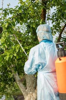 보호복을 입은 여성 농부가 곰팡이 질병이나 해충으로부터 사과 나무를 뿌리고 있습니다.