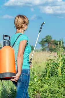 청바지와 티셔츠를 입은 여성 농부는 자연 배경이 있는 정원에서 압력 분무기로 감자 식물을 곰팡이 질병이나 해충으로부터 보호하고 있습니다