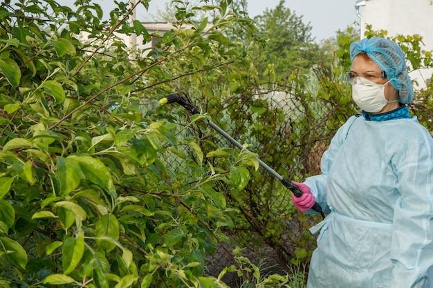 보호 마스크와 양복을 입은 여성 농부가 봄 과수원에서 압력 분무기와 화학 물질로 곰팡이 질병이나 해충의 사과 나무를 뿌리고 있습니다.