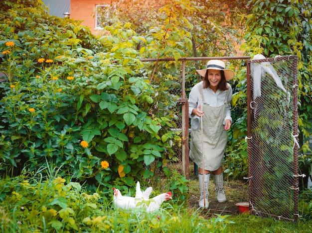 막대기를 든 여성 농부는 푸른 잔디의 닭장에서 방목 닭을 풀어주고 있습니다.
