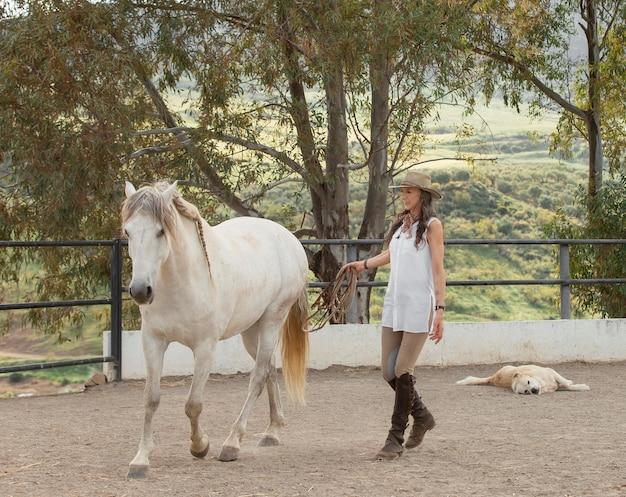 牧場で彼女の馬と女性農夫